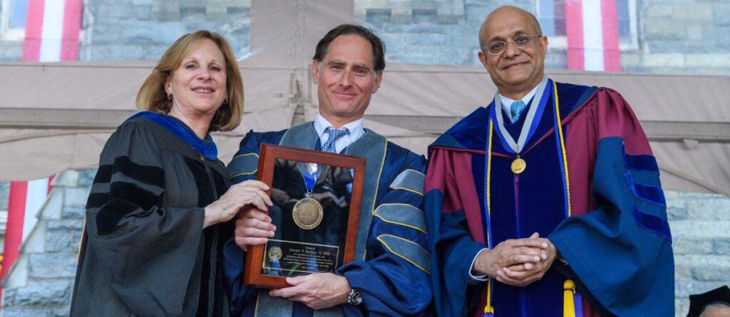 Joseph Baratta (center) receives the Dean's Medal from Pietra Rivoli and Paul Almeida