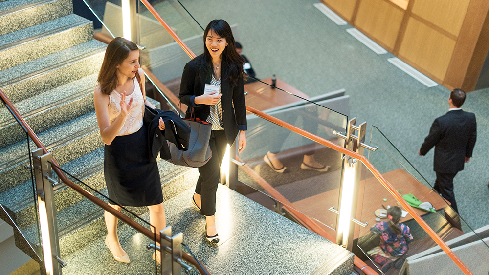 Two women MBA students walk down the stairs at the McDonough School of Business