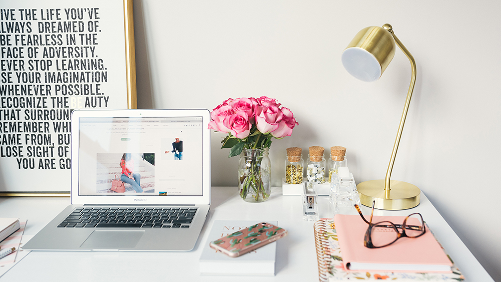 Laptop open on desk at home, with gold lamp, flowers, and notebooks
